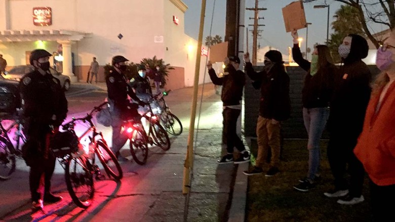 Counterprotesers face San Diego police at Mission and Hornblend in Pacific Beach near end of dueling demonstrations.