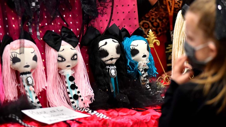 A young girl looks over dolls with a dark side at the Oddities and Curiosities Fair at the Del Mar Fairgrounds.