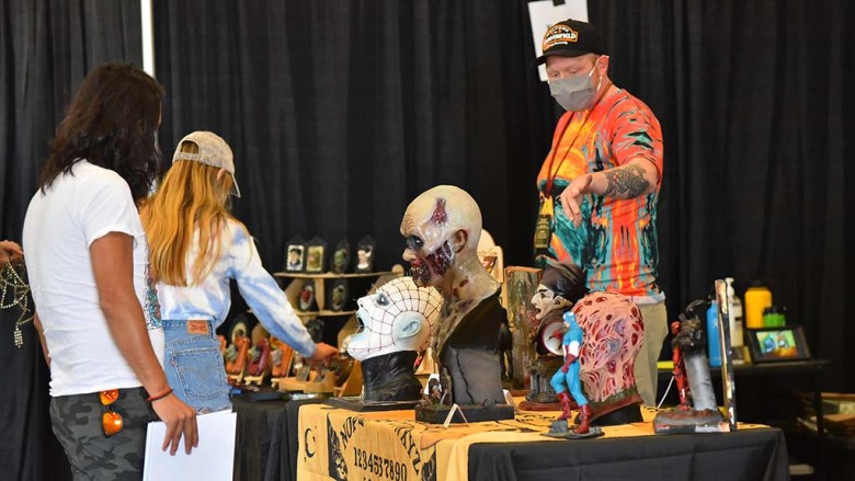 Vendor Fester Crain shows his products to customers at the Oddities & Curiosities Expo at the Del Mar Fairgrounds.