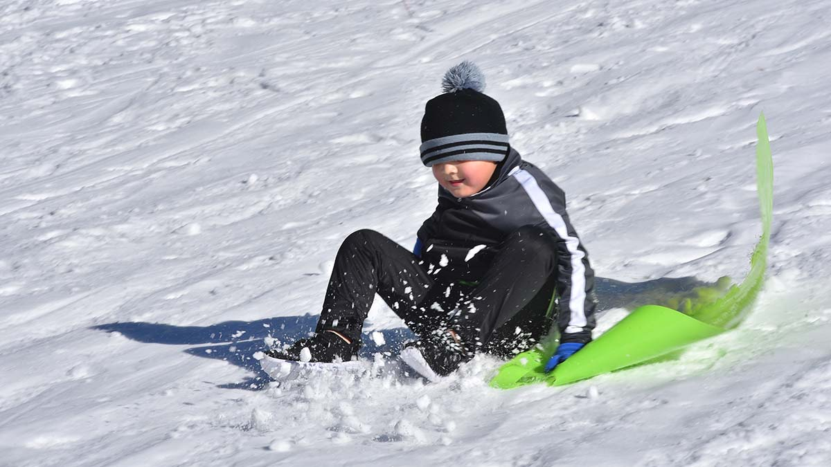 A youngster makes a sightless descent down the hill on a piece of plastic.