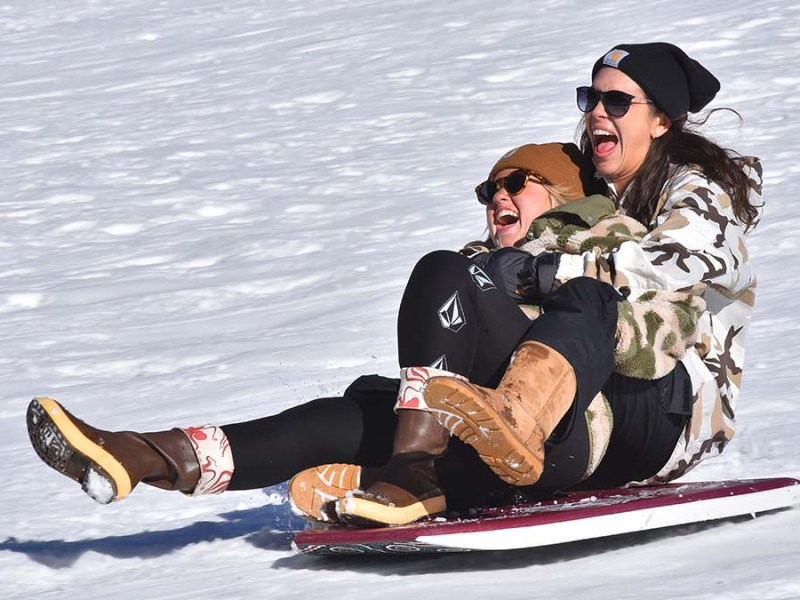 Taylor McCabe (left) and Katie Anderson from San Clemente enjoy their speedy ride down the snowy hill in Mt. Laguna.