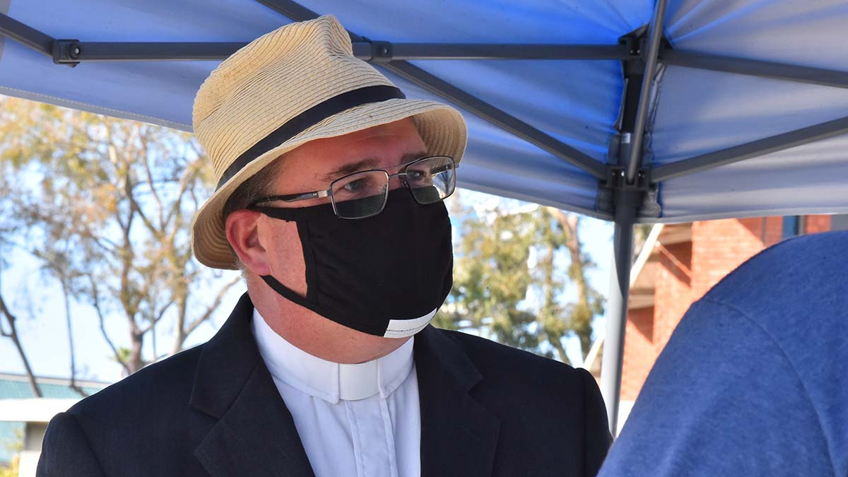 """Senior Pastor, Rev. Dr. Jonathan Doolittle at Clairemont Lutheran Church says a prayer for a man who received ash at the Ash Wednesday drive-in """"Ashes to Go."""""""