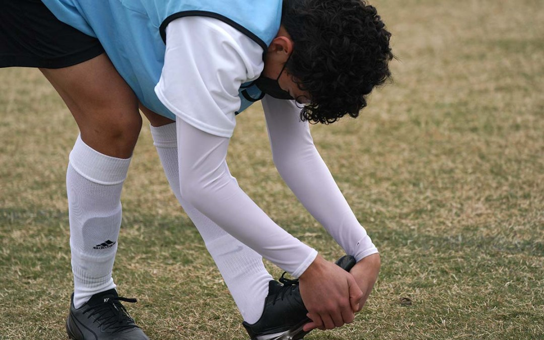 A young man trying out to become a San Diego Loyal soccer player, stretches before a game.