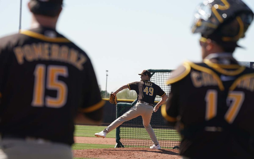 Michael Baez pitches while Drew Pomeranz and catcher Victor Caratini watch