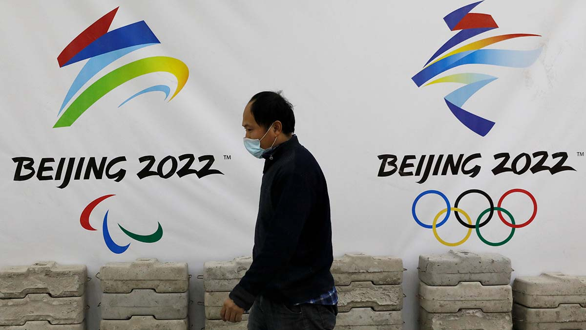 A man walks past a board with logos of 2022 Winter Olympic Games, at a souvenir shop under renovation in Beijing, China.