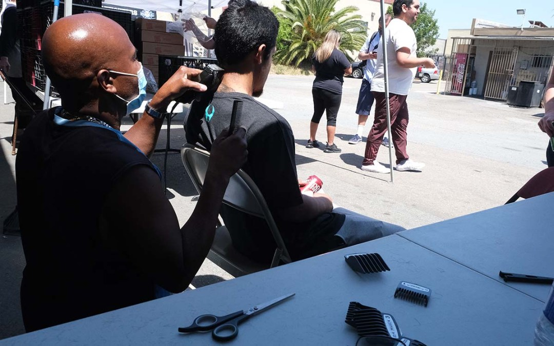 Donald James, an auto detailer, gives haircuts to men and women at the Project Refresh event in Chula Vista.
