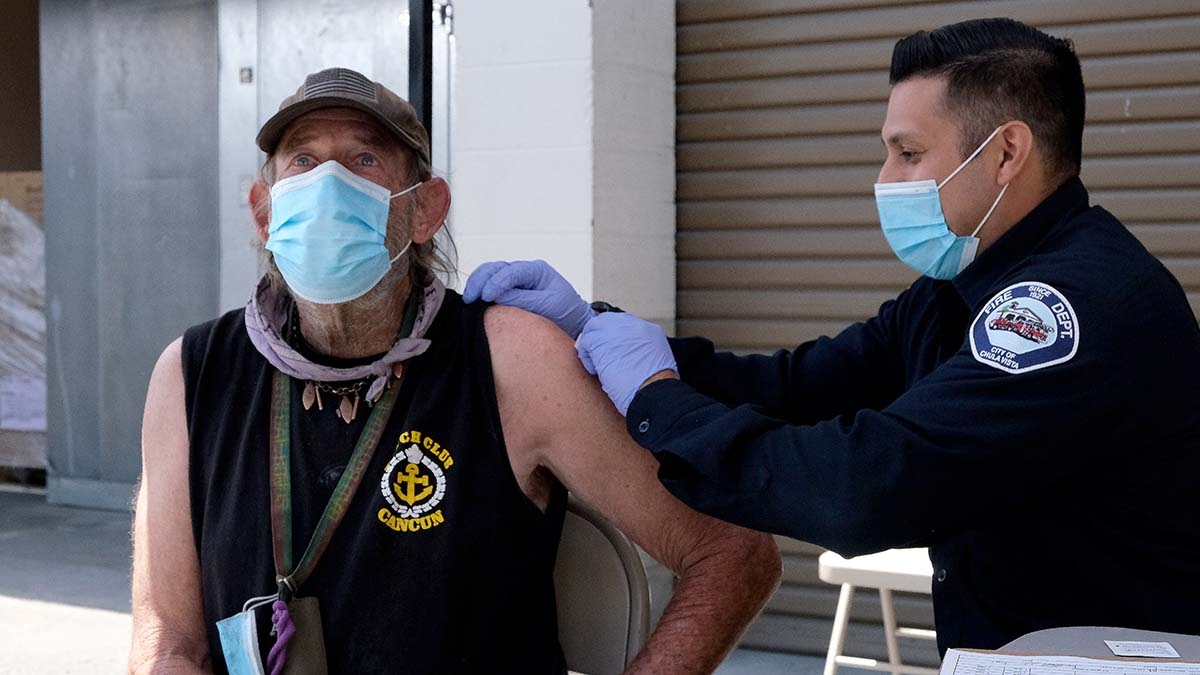 Chula Vista firefighter Matt Garcia prepares to give a Pfizer COVID-19 vaccine to a homeless man.