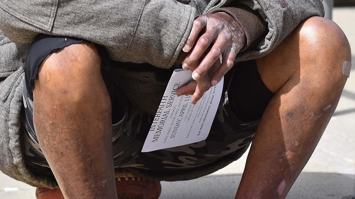 A homeless man holds a program for a interfaith memorial service for three homeless men.