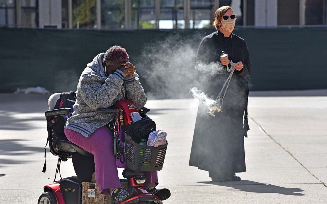 Canon Lisa Churchill of St. Paul's Episcopal Cathedral burns incense near Amber Joseph, who eulogized a homeless friend.