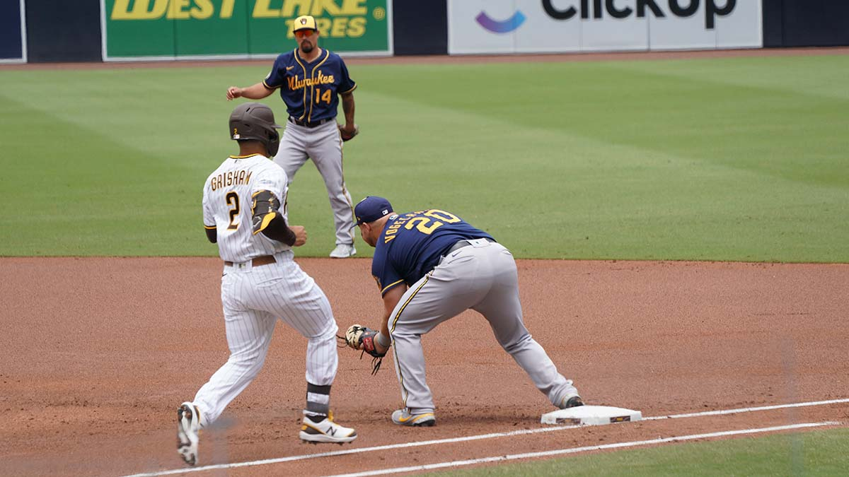 Trent Grisham tries to beat out the tag at first base.