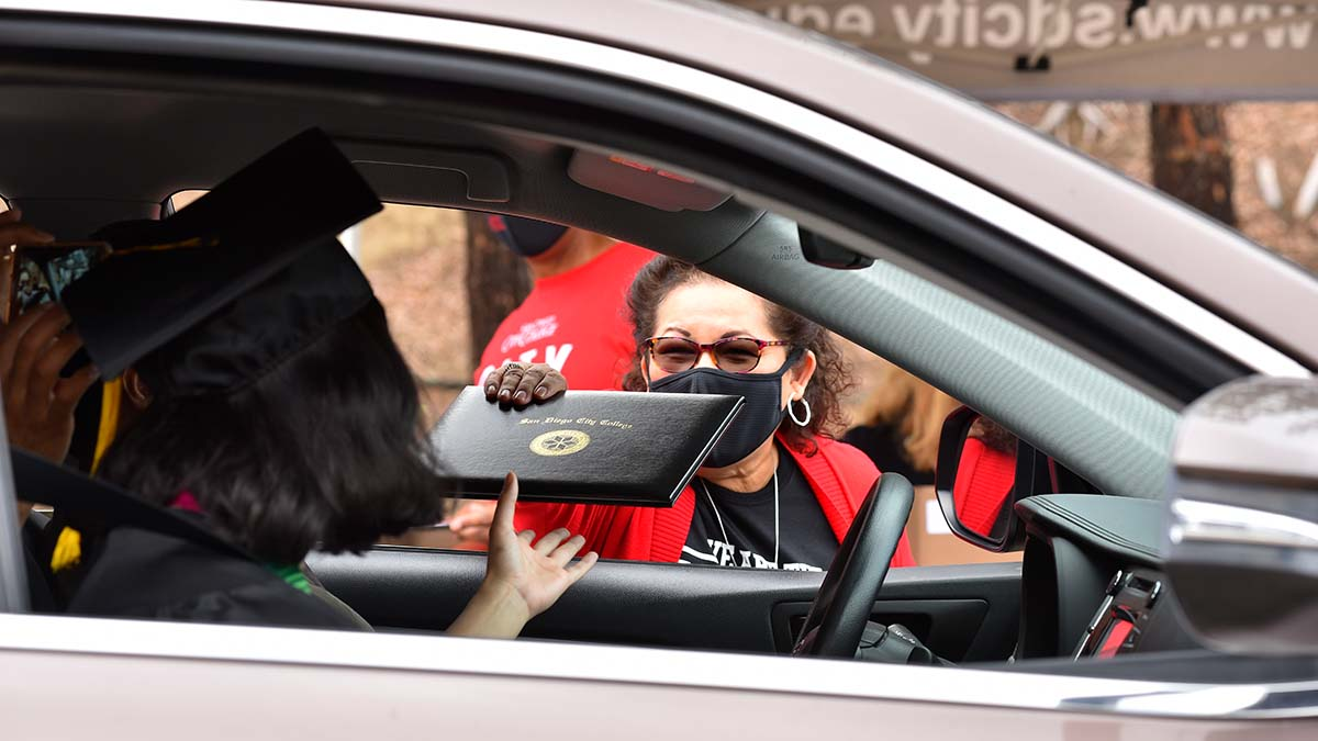 Tillie Chavez, vice president of instruction for City College, hands a letter of congratulations to a graduate in the drive-thru commencement event. Photo by Chris Stone