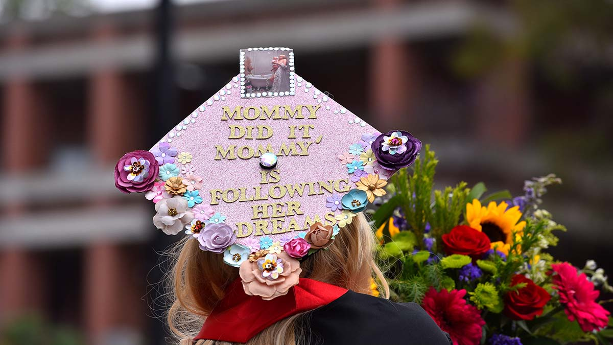 A graduate touts her double duty achievement of being a mom and a student. Photo by Chris Stone