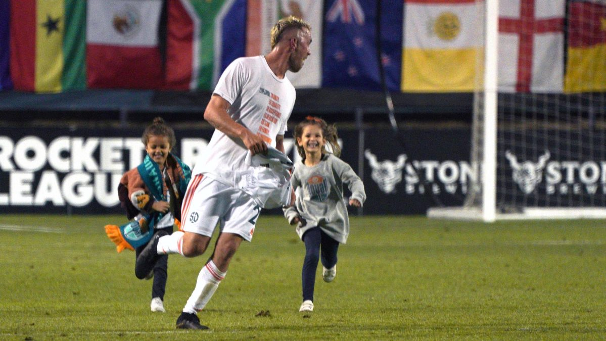 Children try to catch Corey Hertzog on the pitch after the match . Photo by Chris Stone