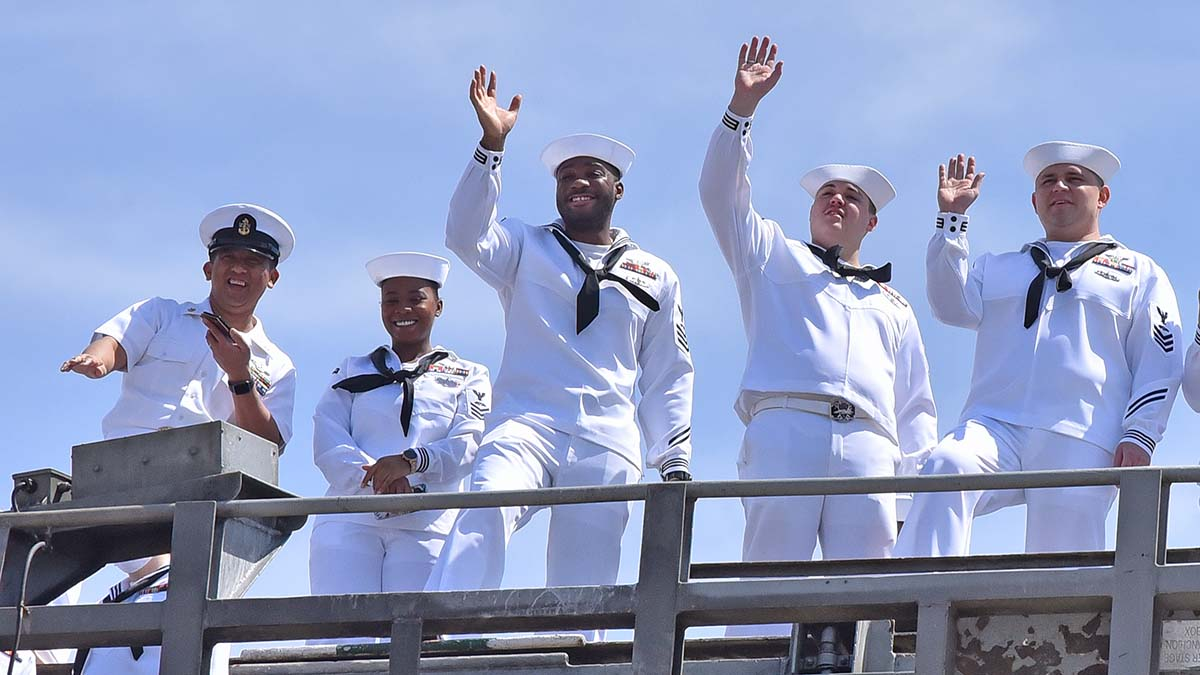 Crew members wave to loved ones on the pier below as the USS Theodore Roosevelt returns after a seven-month deployment. Photo by Chris Stone