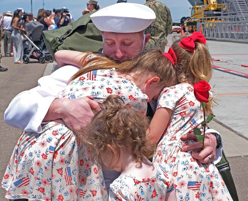 Joshua Mapes is surrounded by hugs from his daughters as he returns home after a seven-month deployment. Photo by Chris Stone