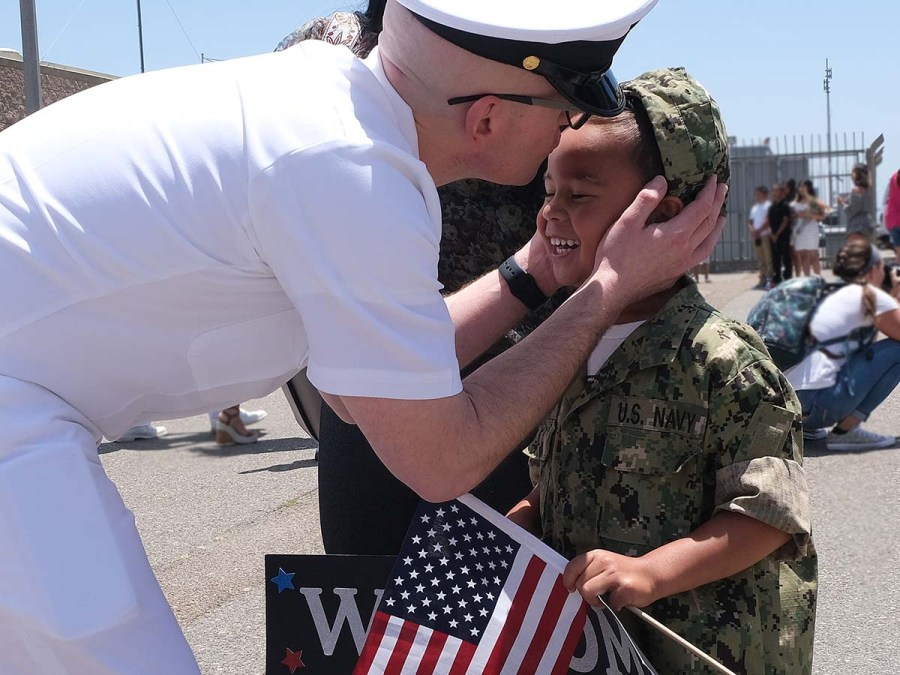 Chief Dan Ezell greets five-year-old son Evan who waved a flag and held a sign welcoming Dad home. Photo by Chris Stone