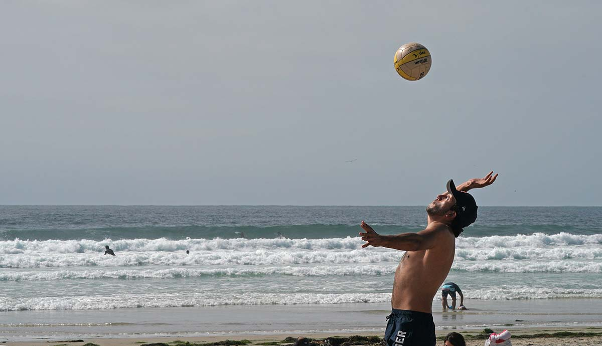 A volleyball players serves the ball during a busy Saturday at La Jolla Shores. Photo by Chris Stone