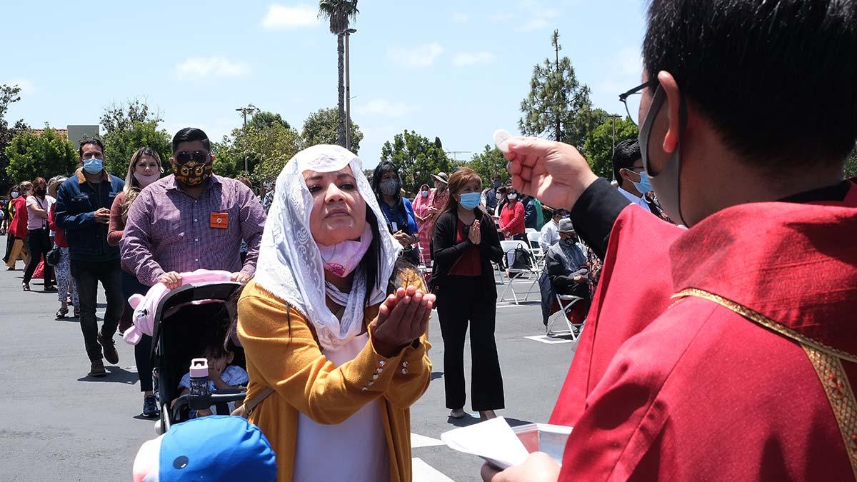 The Very Rev. Michael Pham distributes Holy Communion. Photo by Chris Stone