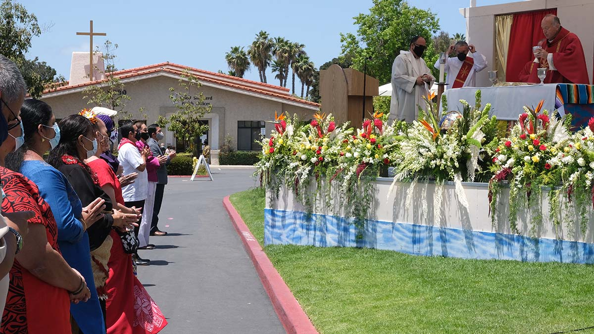 Representatives of 20 cultures line up in front of the altar at an outdoor Mass. Photo by Chris Stone