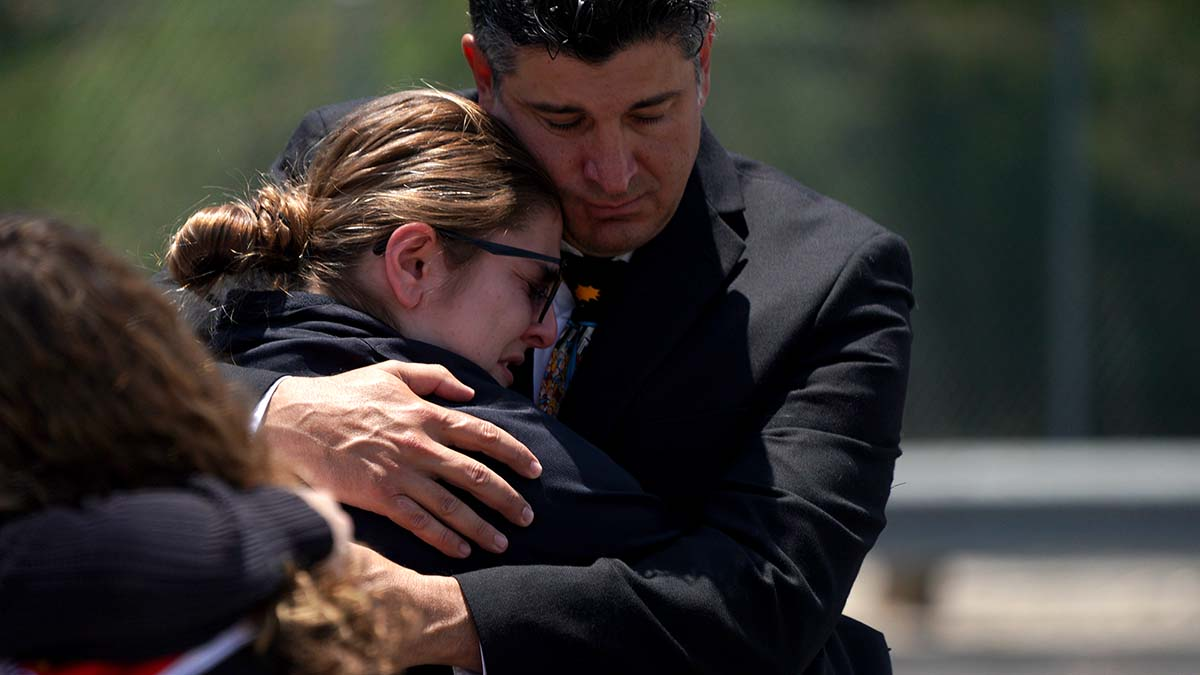 Alex Morrison, best friends to the Parks, comforts a coach of the San Diego Angels hockey team. Photo by Chris Stone