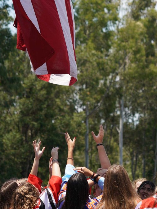Members of the San Diego Angels hockey team reach to bring down a flag. Photo by Chris Stone