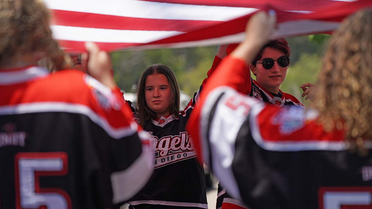 Members of the San Diego Angels hockey team hold a flag given to them by the fire department. Photo by Chris Stone