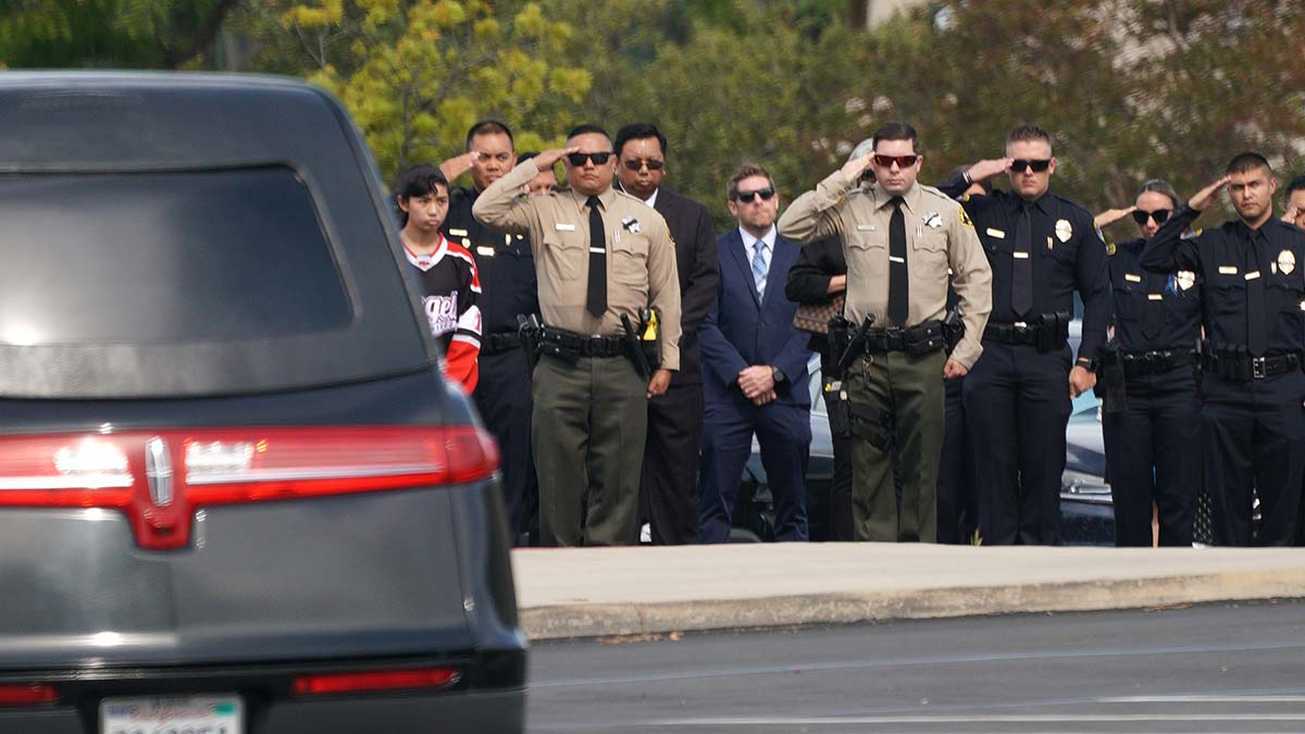 Law enforcement officers salute as the casket of Ryan Park and Jamie Huntley-Park is taken into the chapel. Photo by Chris Stone