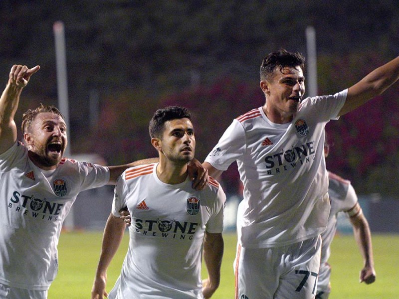 Jack Metcalf, Alejandro Guido and Miguel Berry (left to right) celebrate in front of the Locals section after Guido scored a goal. Photo by Chris Stone