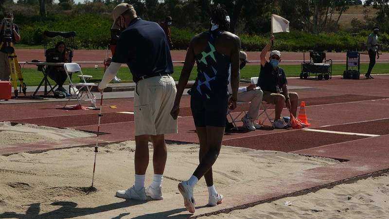 Local USATF official Gary MacDonald with a white flag, signals a fair Brittney Reese jump.