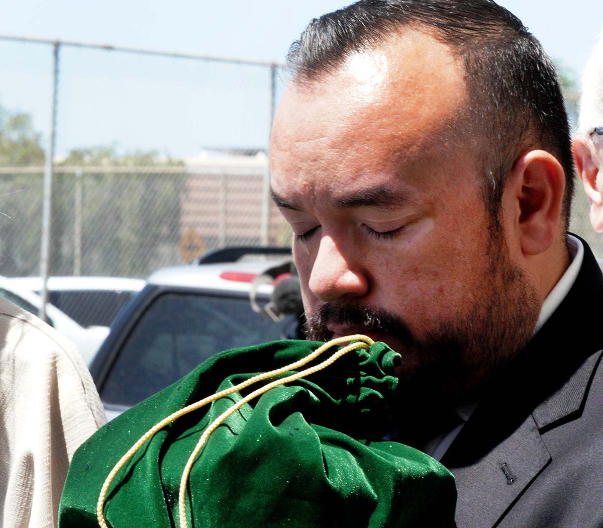 Jose Gonzalez, personal assistant to Fr. Joe Carroll, clutches his remains in tears after the funeral.