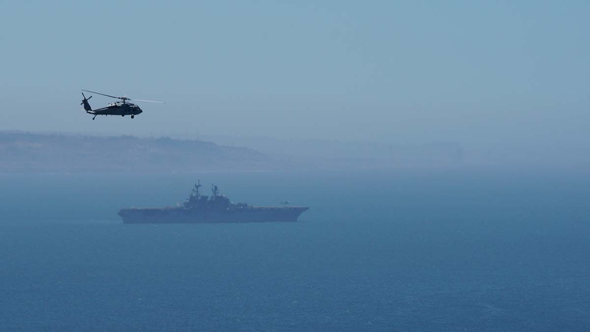 A helicopter flies over the USS Tripoli amphibious assault ship, part of the Carl Vinson strike group. Photo by Chris Stone