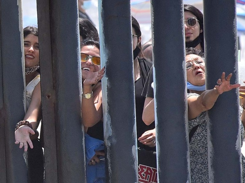 Seven members of Francy Carbajal's family gather on the Mexican side to wave to her. Photo by Chris Stone