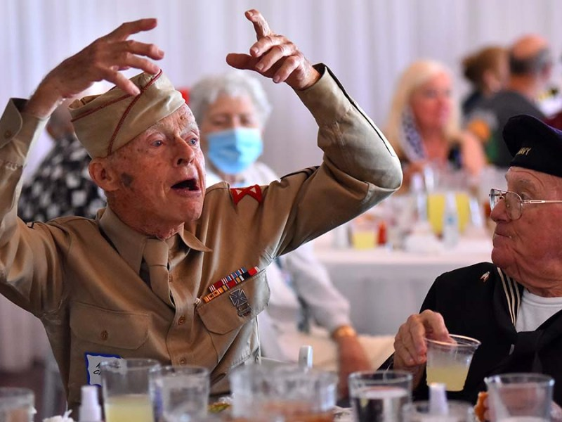 World War II Army veteran Andres Chappaz, (left) tells a story to fellow veterans. Photo by Chris Stone
