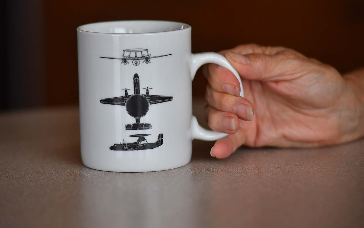 Marilyn Adams shows a mug depicting the AWACs planes her son flew in.