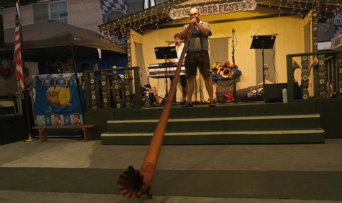 A member of Guggenbach-Buam, from Baden-Württemberg, German plays the alphorn at the ElCajon Oktoberfest. Photo by Chris Stone