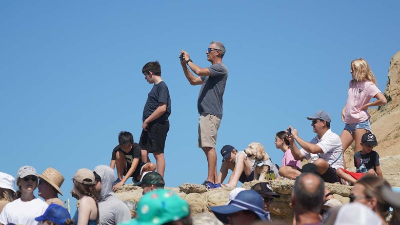 Hundreds of spectators perch on cliffs and line the competition area to watch the Surf Dog Surf-a-thon in Del Mar.