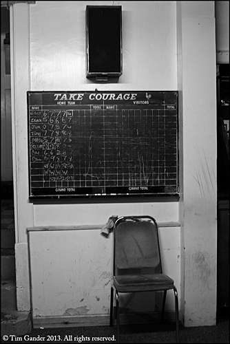 Pub skittle score board hangs on the wall above a chair, music speaker above that