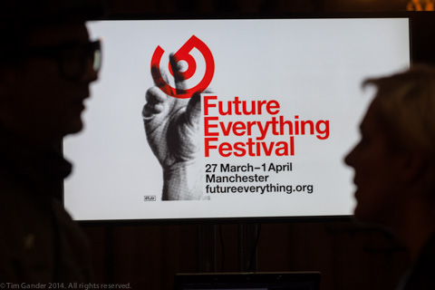 Two silhouetted faces in profile talking with Future Everything Festival signage displayed between them