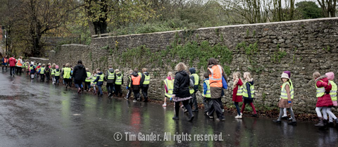 A line of school children in high-visibility vests make their way along a village road in the rain.