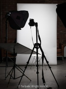 A portrait photography setup with lights, backdrop and camera on a tripod.