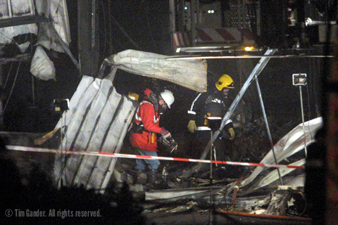 firecrews examine the wreckage of an aircraft after it crashed into an industrial building near Aldershot.