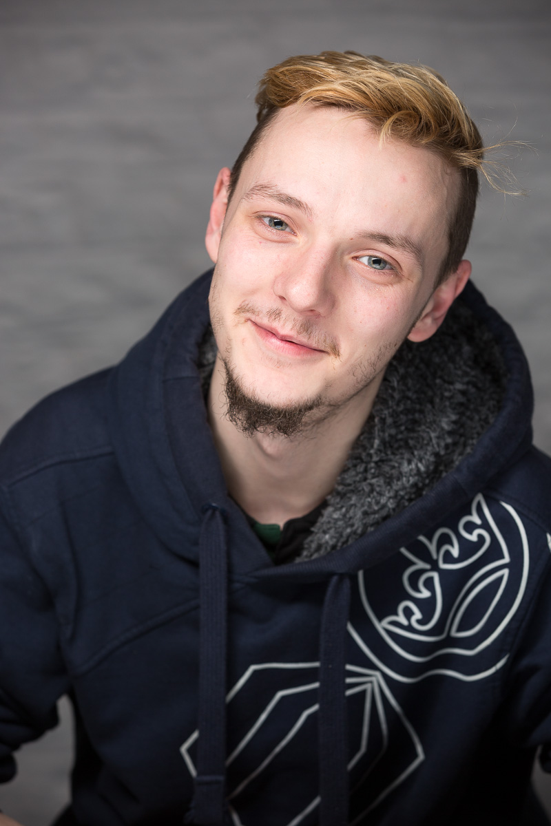 Portrait of a young man, smiling to camera, wearing a hoodie.