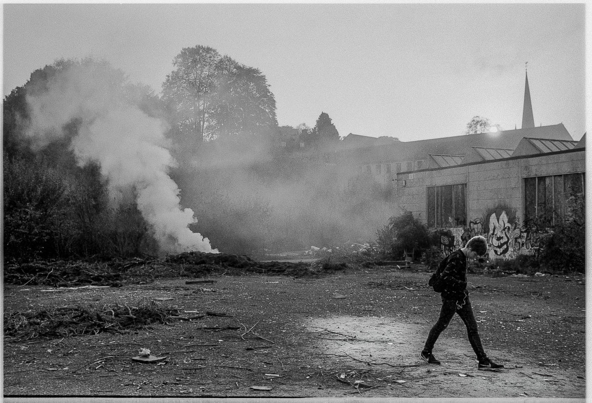 Black and white view of a youth striding off to the right of an open area while to the left in the background a bonfire burns, a thick column of smoke rising into the late afternoon light.