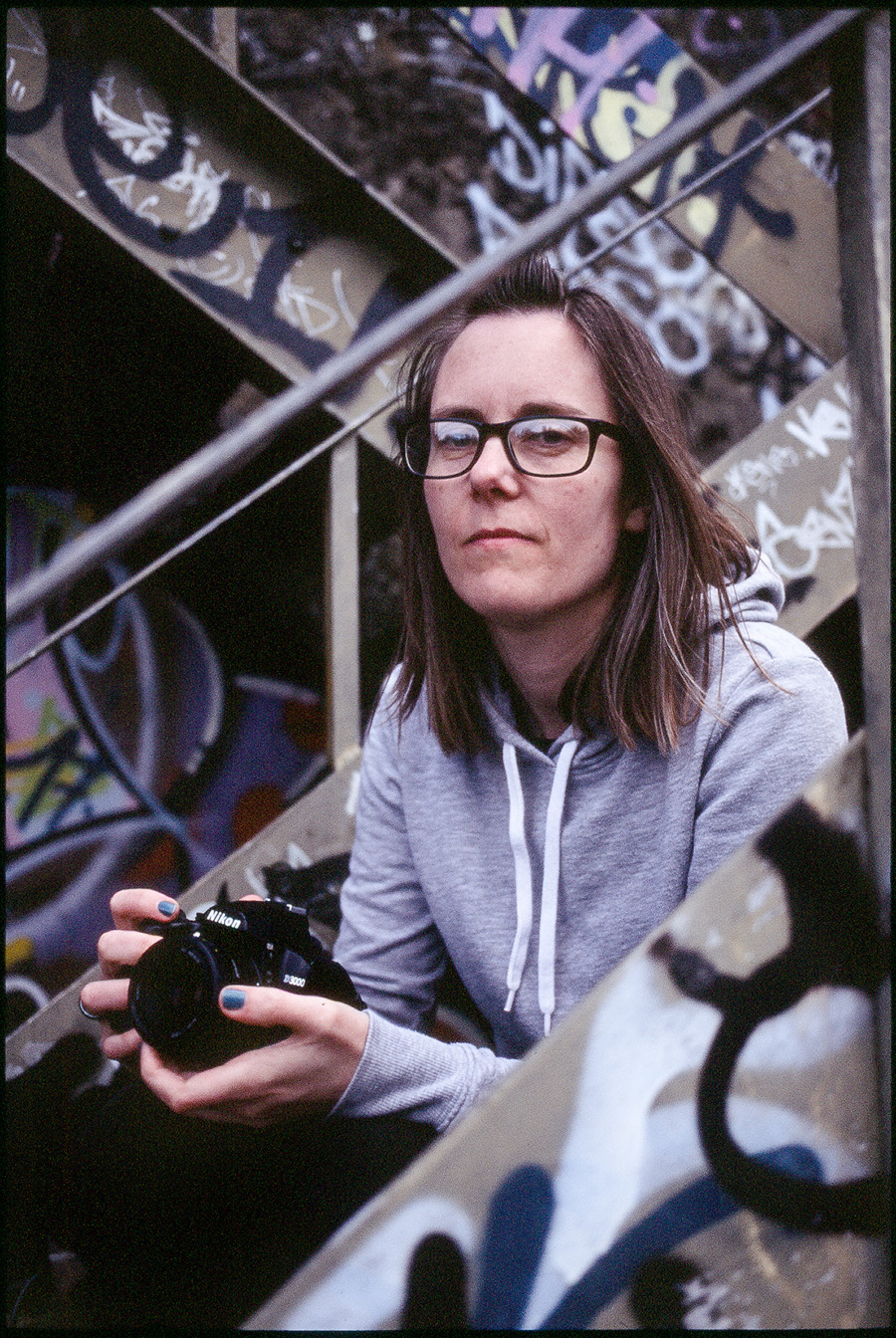 A woman sits on a metal staircase framed by its graffiti-covered rails, holding a camera, wearing glasses and a grey sweat top.