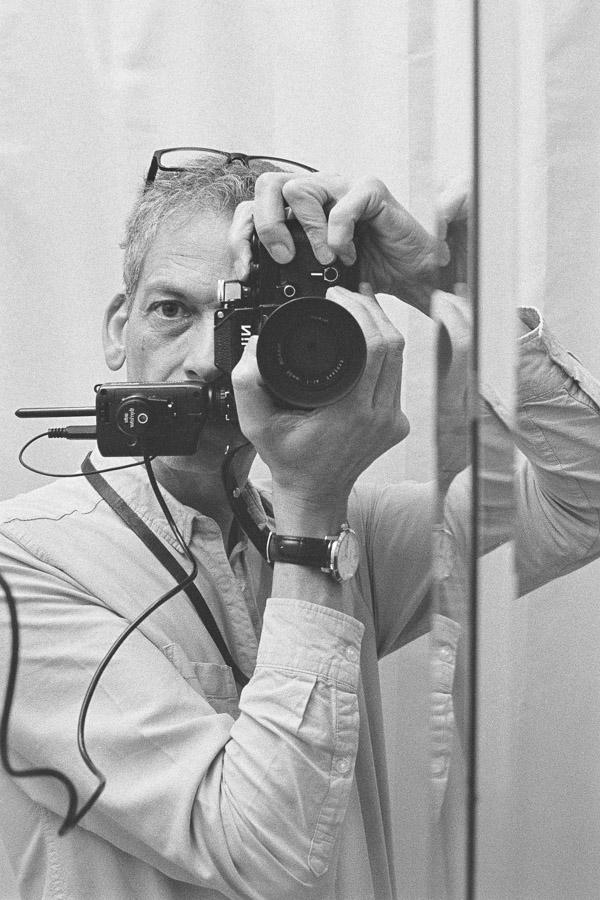 Self-portrait of Tim Gander with Nikon F2 camera in bathroom mirror.