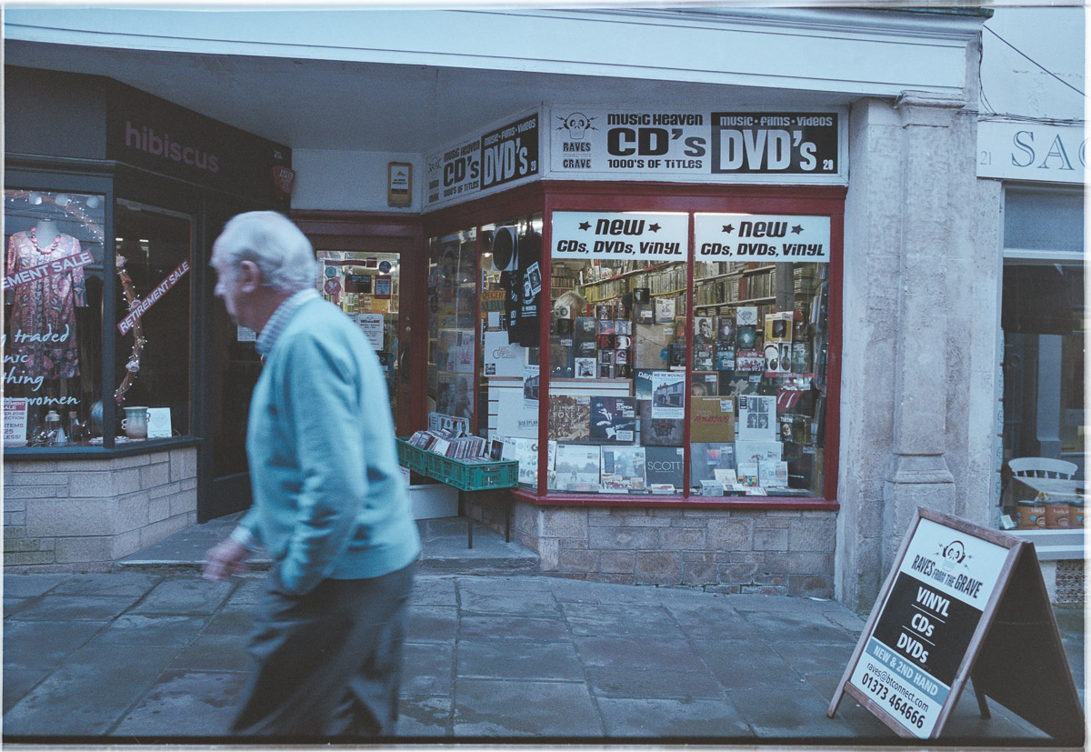 View of the shop front as a gentleman in a turquoise sweater walks past.