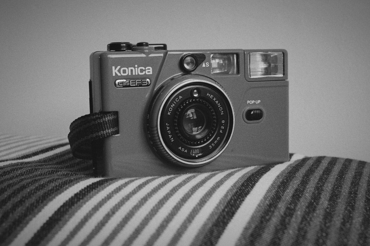 Photo of a Konica C35 EF3 camera on a stripy cushion.
