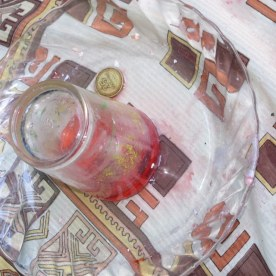 """This is the activity in which a candle under a cup in a dish of water sucks the water up into the cup. The group put on a nice twist, calling it: """"Pick the coin out of the water without getting your finger wet."""" Here you can see the coin, high and dry, after the red water has moved up into the cup."""