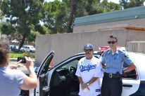 Cole Howard, right, a Placentia police explorer, let members of the community check out the police car.