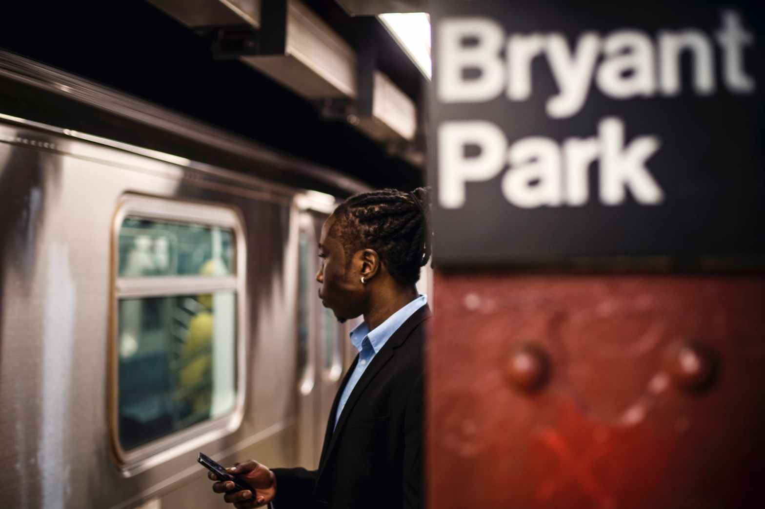 serious man with smartphone on new york subway